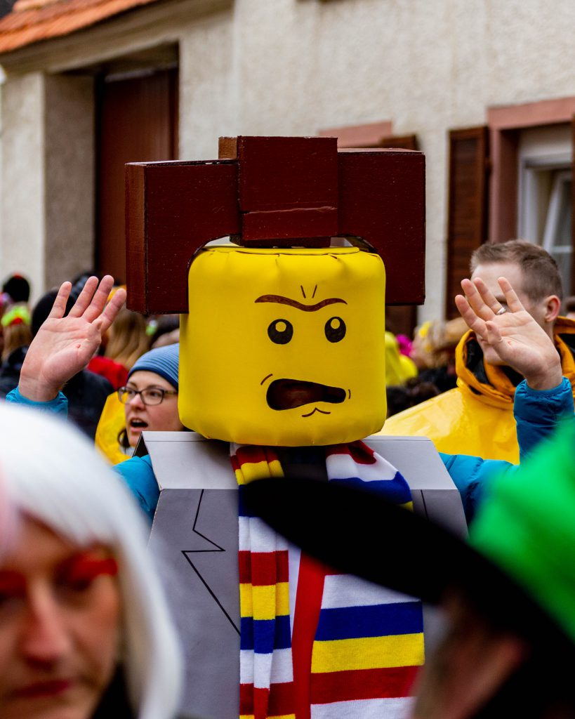 Karnevalist*in im Lego-Kostüm