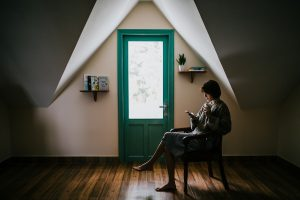 Die perfekte Lernumgebung: Frau auf Stuhl mit Holzdielen und grüner Tür.