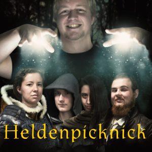 """Michael hält die Hände wie ein Marionettenspieler über die vier Portraits von Lena, Robin, Viktoria und Moritz in """"heldenhafter"""" Verkleidung, darunter steht das Wort Heldenpicknick in gelb"""