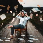 Ein junger Mann schützt sich auf einem Stuhl sitzend mit einem Buch vor fallenden Zetteln