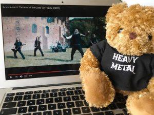 Metal-Teddy vor einem Laptop auf dem ein Metal Musikvideo läuft
