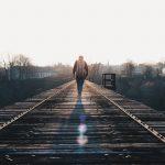 Eine Person geht allein ein Bahngleis entlang
