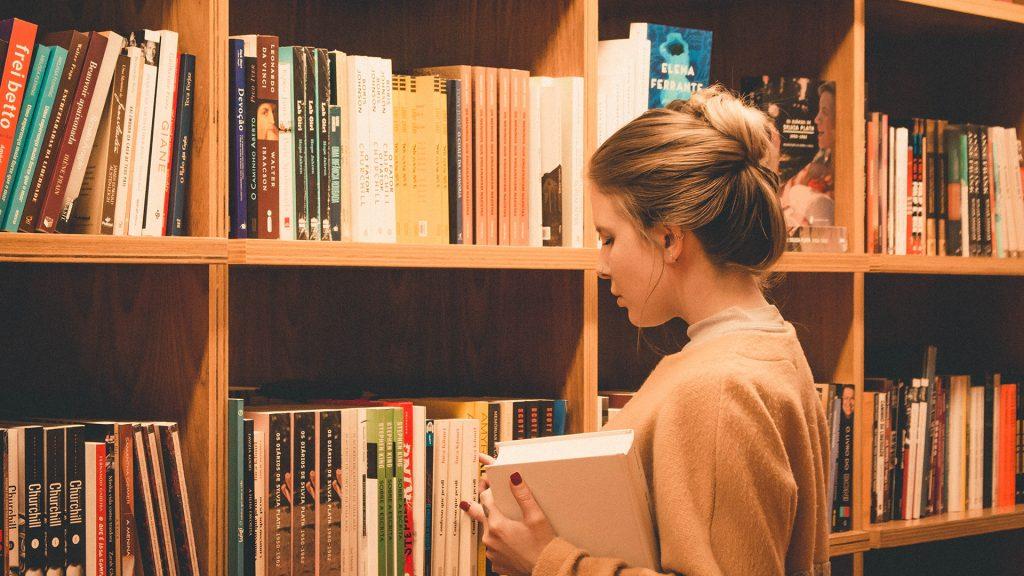 Frau räumt Bücher weg
