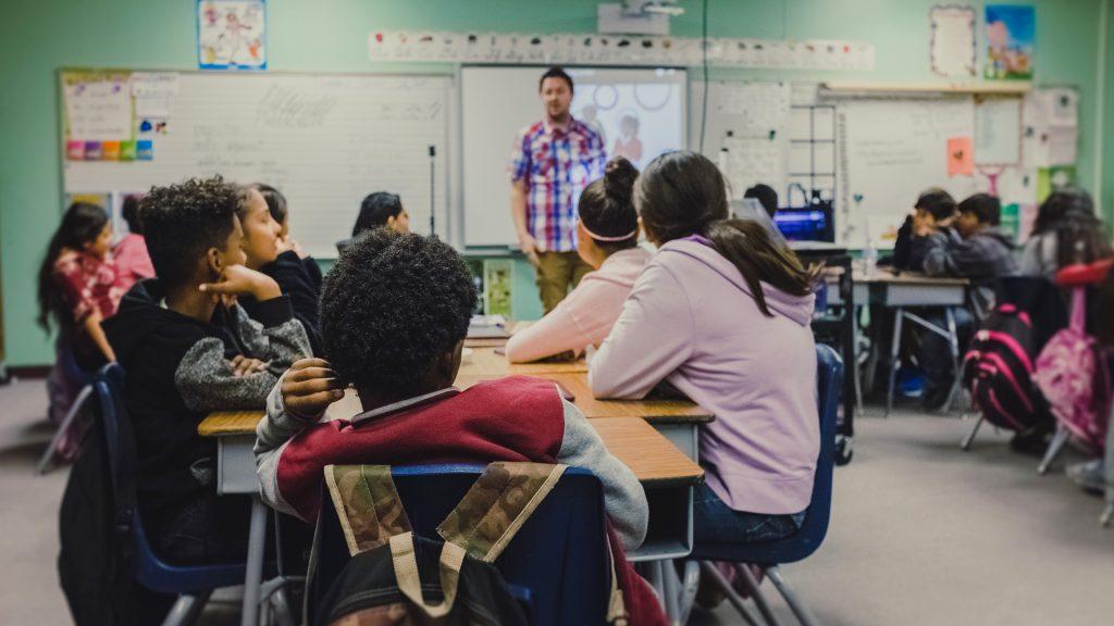 Eine Schulklasse. Der Lehrer erklärt etwas.