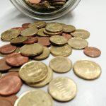 Münzen geringen Wertes, die aus einem Glas geschüttet wurden