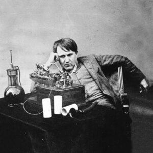 Thomas Edison sitzt vor einer frühen Version seines Phonographen, er wirkt konzentriert. 1888
