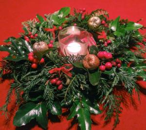 Ein winterlicher Kranz mit einer Kerze in der Mitte. Der Kranz ist aus Thuja, Ilex und Tanne gebunden. Geschmückt ist er mit roten Beeren, goldenen Dekoäpfeln und roten Schleifchen.