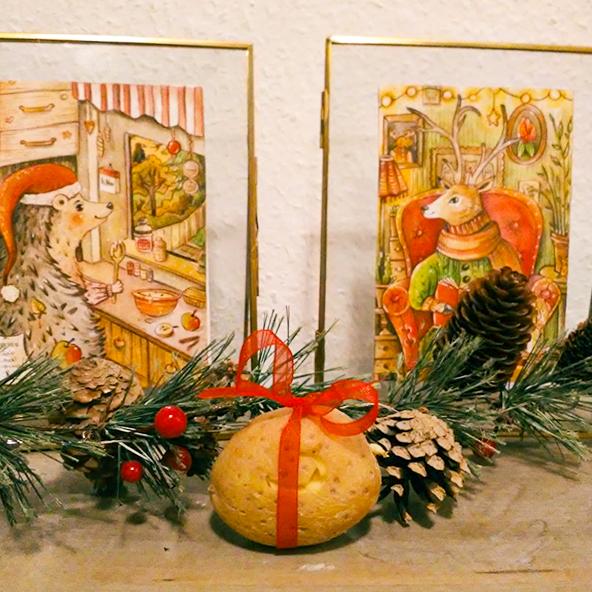 Man sieht eine Kartoffel. Sie ist in der Mitte des Bildes platziert und von einem roten Schleifchen gekrönt. Daneben liegen ein Tannenzapfen, Tannengrün und rote Beeren. Im Hintergrund stehen zwei gezeichnete Bilder: Ein Igel, der Kuchen bäckt und eine rote Zipfelmütze trägt und ein Hirsch in einem roten Ohrensessel.