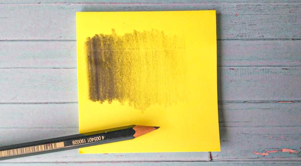 Ein Bleistift liegt auf einem gelben Notizblock. Auf dem Blatt Papier ist ein Helligkeitsverlauf von dunkel zu hell zu sehen. Einstiegsmaterialien Porträtzeichnungen