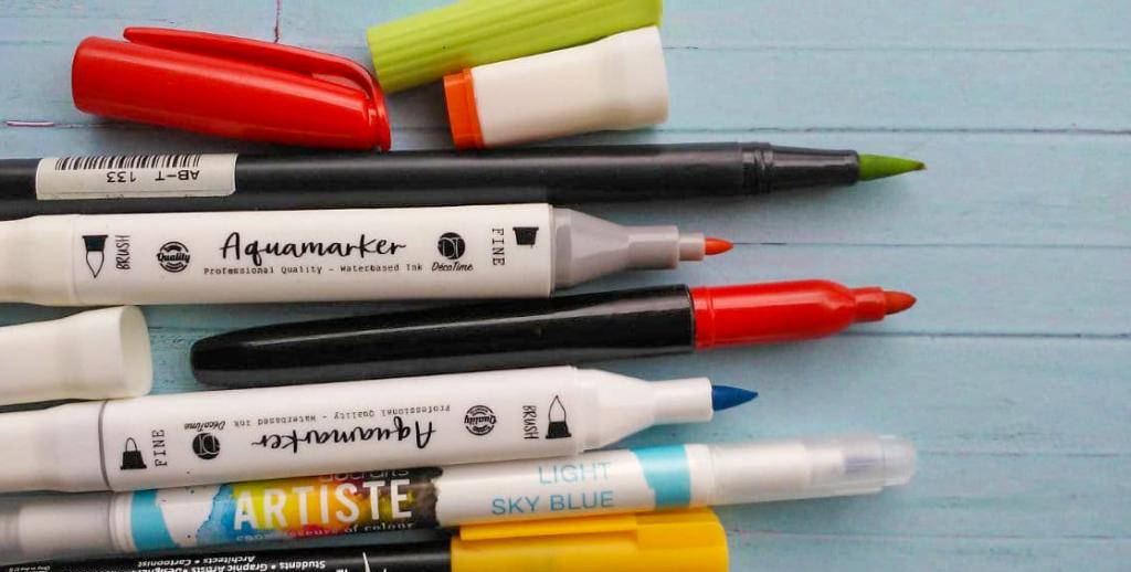 Einige Marker mit geöffneten Kappen. Die Marker sind von verschiedenen Marken und haben unterschiedlich feine, grobe und flexible Spitzen. Die Stifte haben unterschiedliche Farben: rot, grün, orange, gelb und blau. Einstiegsmaterialien Porträtzeichnungen