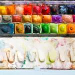 Ein Aquarellfarbkasten mit einer Palette zum Mischen. Der Kasten ist benutzt und einige Farben sind bereits zu großen Teilen abgenutzt. Die Näpfchen sind vage nach Farben geordnet. Der Kasten ist aus Metall und wurde offensichtlich schon häufiger zum Aquarellieren benutzt.