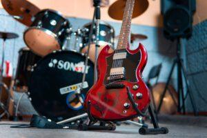 Eine rote E-Gitarre steht auf einem Ständer. Im Hintergrund ist ein Schlagzeug unscharf zu erkennen