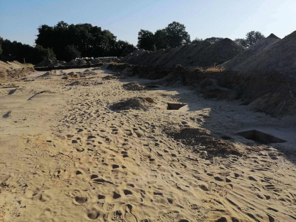 Im Vordergrund Sandboden mit einigen recheckigen Löchern. Im Hintergrund eine 1m hohe Kante aus dunklerem Erdreich, auf der hohe Mieten (= Hügel) von ebenso dunklem Erdreich liegen.