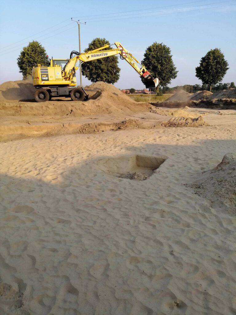 Im Vordergrund Sandboden mit recheckigen Löchern. Im Hintergrund ein Bagger, der in dünnen Schichten den Hummus und den Zwischenboden abzieht.