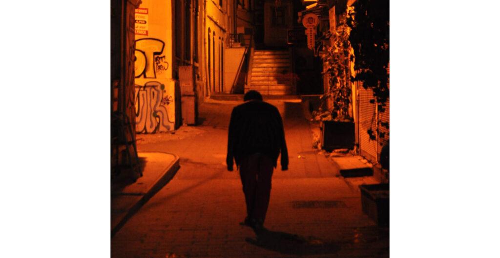 Ein Mann läuft eine nächtliche Gasse mit Graffitti an den Wänden hinab