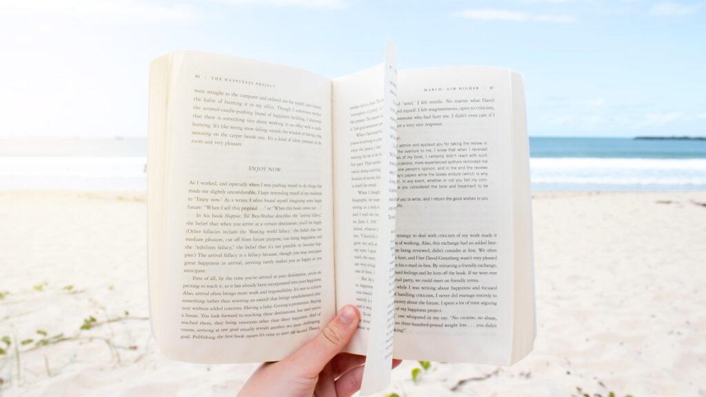 Ein aufgeschlagenes Buch wird in die Kamera gehalten, im Hintergrund ein Strand und ein Meer